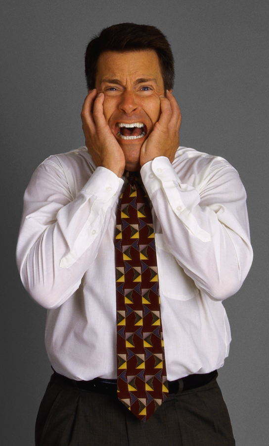 Businessman Clasping His Face in Horror