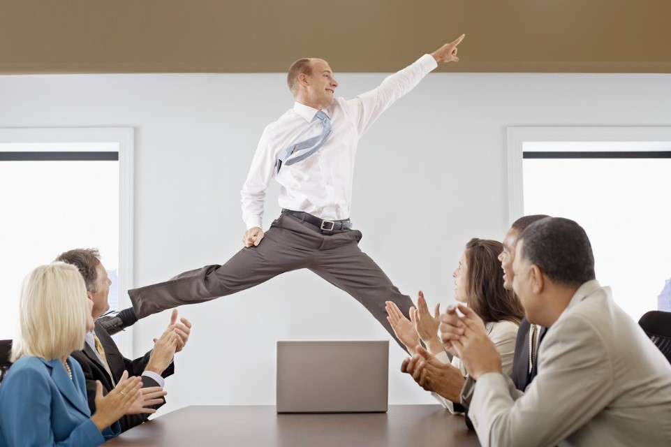 Business man jumping and pointing with excitement at the head of a business meeting