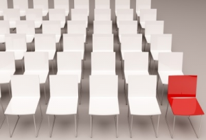 Rows of white chairs with one red chair