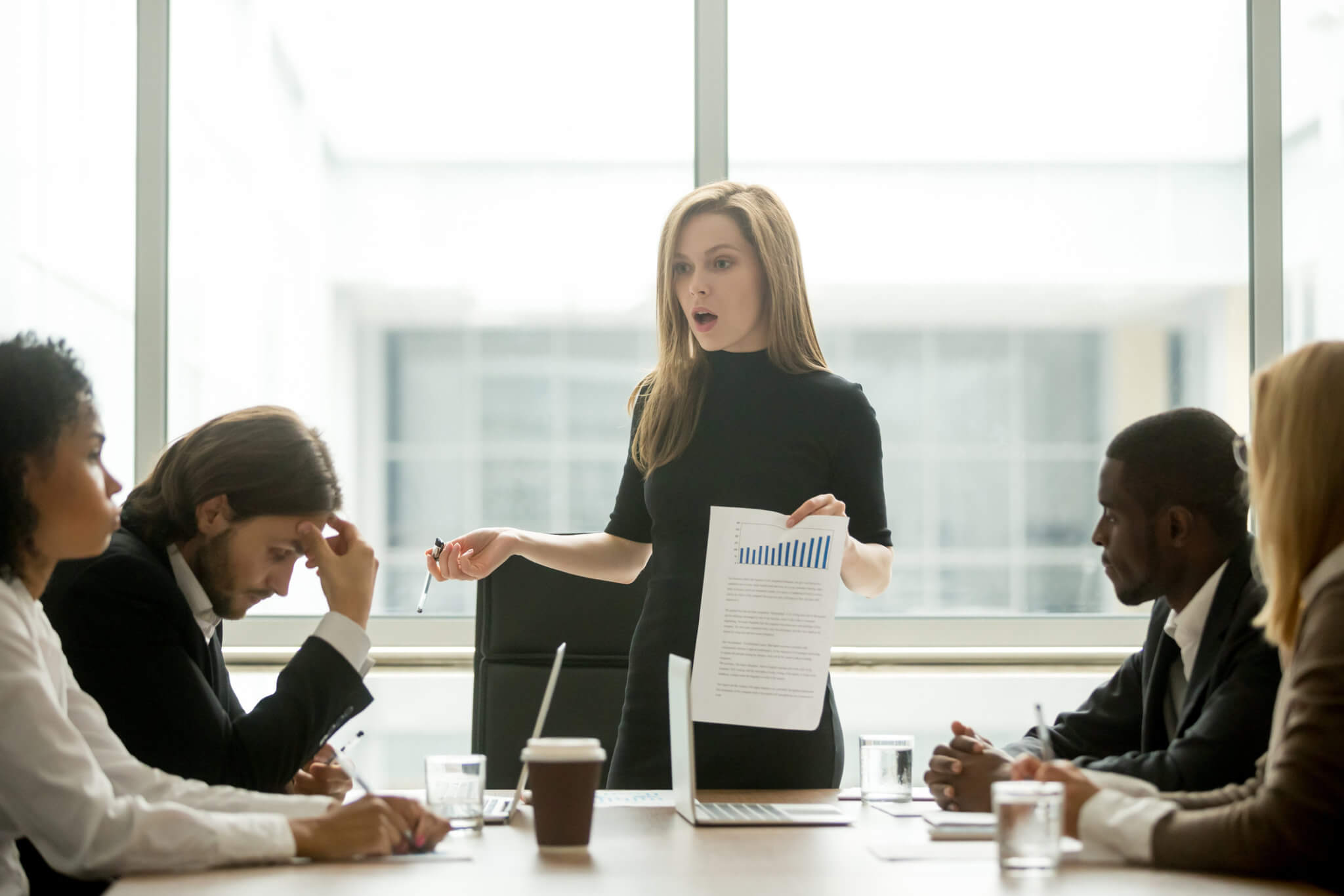 Angry female executive venting to employees in a meeting